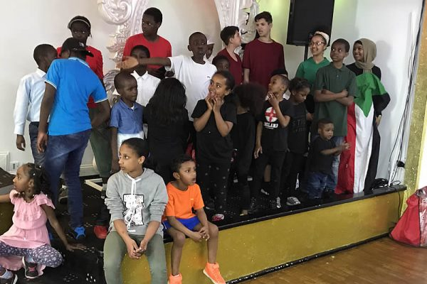 Waging Peace - [Kids listen on, far right draped in Sudanese flag]